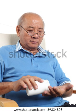Asian senior man spilling pills onto hand. Isolated on white background.