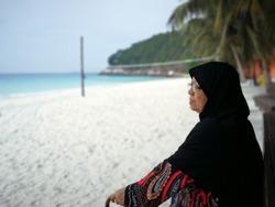 Asian senior Muslim woman sitting by the beach.