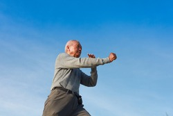 Asian Senior old man practice Taichi Chinese Kungfu on the beach