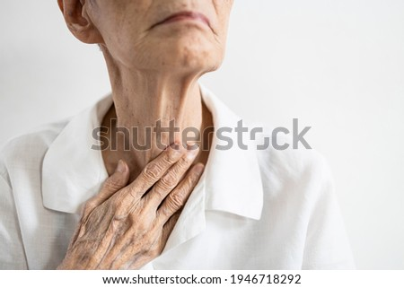 Asian senior patient touching neck with her hand,old elderly has sore throat,foreign body stuck in throat,painful swallowing,pain cough,inflammation of the larynx,throat problems or laryngitis disease Photo stock ©