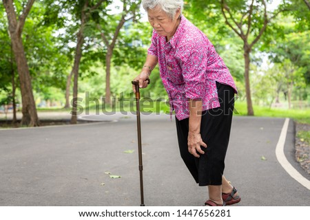 Asian senior woman arthritis,osteoarthritis,elderly people walking with walker in outdoor park,holding hand on the knee,feeling pain in the knee,swollen knees,leg hurt,medical and healthcare concept