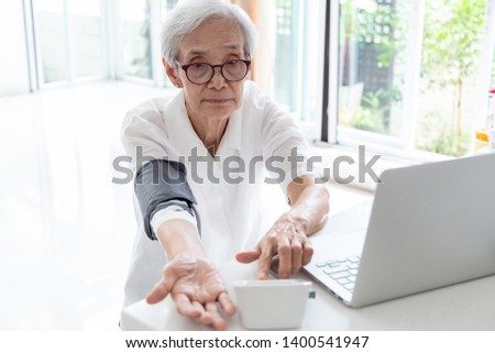 Asian senior woman checking blood pressure at home, elderly people check health using a blood pressure monitor, checking patients blood pressure measurement by yourself,health care concept