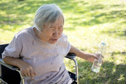 Asian senior woman choking on water,elderly people with poor quality water,bad smell and dirty of water, smelled plastic causing her to spitting out the water while drinking from plastic bottles