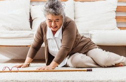 Asian senior woman falling down lying on floor at home alone. Elderly woman pain and hurt from osteoporosis sickness or heart attack. Old adult life insurance with hearlth care and treatment concept