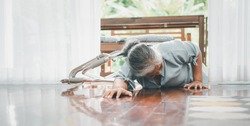 Asian senior woman falling down on lying floor at home after Stumbled at the doorstep and Crying in pain and asking someone for help. Concept of old elderly insurance and health care