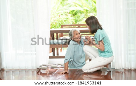 Asian senior woman falling down on lying floor at home after Stumbled at the doorstep and Crying in pain and the nurse came to help support. Concept of old elderly insurance and health care Stock photo ©
