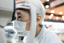 Asian senior woman having eyesight test using tonometer looking into the machine,old elderly patient checks her vision,eye examination by ophthalmlogist,presbyopia problems,health care at eye clinic