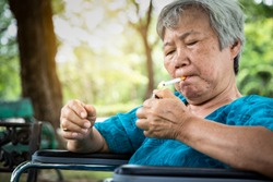 Asian senior woman holding a cigarette smoking,elderly smoker in wheelchair,smoking is dangerous to health,causes various serious diseases,cancer,emphysema,addicted to cigarettes and difficult to quit