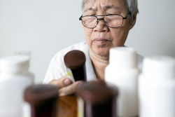 Asian senior woman holding drug bottle in front of medicine cabinet in her home,reading the label on a bottle for medical treatment,old elderly checking expiration date or deterioration of medication