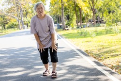Asian senior woman is extremely tired while walking at park, body is weak feeling tired easily due to lack of energy and don't exercise very often, exhausted elderly people have the symptoms fatigue