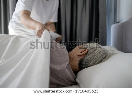 Asian senior woman is sleeping on a bed in bedroom,female caregiver cover senior patient with blanket,assisting old people,putting up the blanket on elderly at nursing home,assistance,care,support
