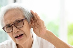 Asian senior woman listening by hand's up to the ear,having difficulty in hearing,elderly woman hard to hear,wear glasses with hearing impairment,hearing impaired old people