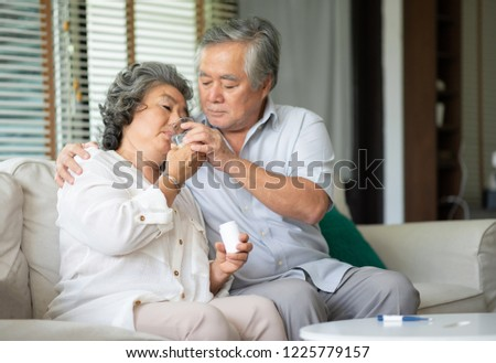 Asian Senior Woman taking medicines and drinking water while sitting on couch. Old man take care his wife while her illness at the house.
