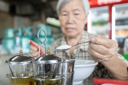 Asian senior woman was using a spoon to scoop white sugar into her bowl of noodles,add flavor to food,eat too much sugar or sweet taste,harm from eating,unhealthy nutrition,concept of obesity,diabetes