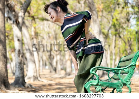 Asian senior woman with back and hip joint painful while standing up,female patient having backache,lumbago pain,hand touch on the hip,elderly suffer from ribbing hurt or waist pain,health problems