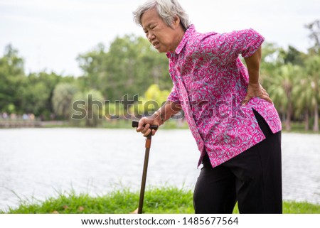 Asian senior woman with hip joint pain while walking,female patient having backache,lumbago pain,hands touching on the hip in outdoor park,elderly people suffering from ribbing pain or waist pain