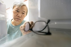 Asian senior woman with memory impairment symptoms,forget her glasses in the refrigerator or storing glasses in the fridge,female elderly having dementia, cognitive impairment, alzheimer's, amnesia