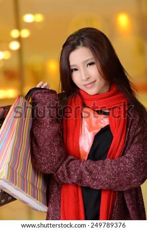 Asian shopping woman holding bags.