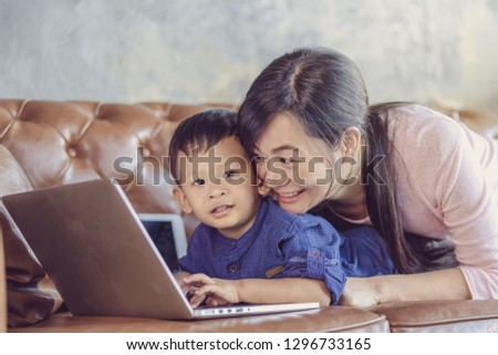 Asian Single mom with son are looking the cartoon via technology laptop and playing together when living in loft house for Self learning or home school,Family home school concept