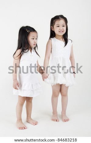 Asian sisters holding hand on plain background