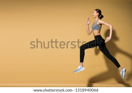 Asian slim Fitness woman exercise warm up stretch spring jumps legs, studio lighting yellow beige mustard background sun shadow copy space, concept Woman Can Do athlete Sport 6 packs #1318940066