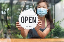 Asian small business owner wearing protective face mask and turning sign to open again after the quarantine due to coronavirus pandemic. Woman hanging open sign on the glass window. Focus on sign.