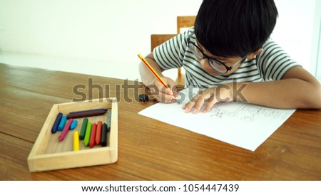 Asian Smart Boy Drawing By Pencil Before Coloring Colorful Crayons In The Wooden Tray Art