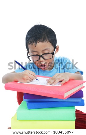 Asian smart boy writing a note over a stack of books. Shot in studio on isolated white