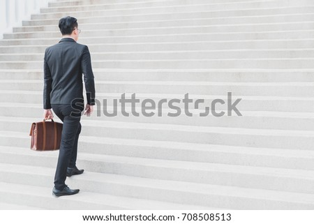 Asian Smart Businessman walking up the stairs.Concept of success business step. #708508513