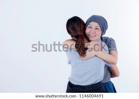 Asian smiling, happy ovarian, breast cancer woman with no hair recovery chemo hug friend, family encouragement, love, care to fight severe disease on white background/ medical health care concept