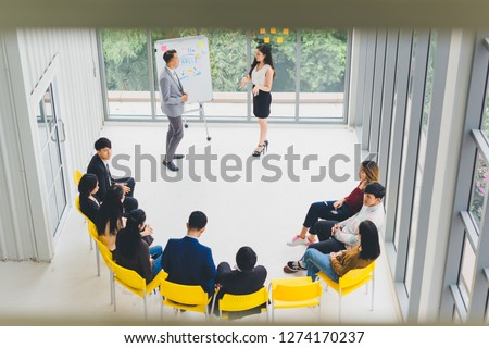 Asian Speaker male and female speaking at seminars and workshops to the people in the meeting. By the participants of the seminar and training sitting round a semicircle. Top view. #1274170237
