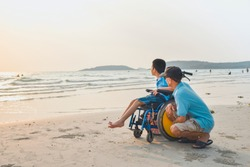 Asian special child on wheelchair and his dad on the beach at sunset, Father helped him to get closer to nature, Life in the education age of disabled children, Happy disabled kid concept.
