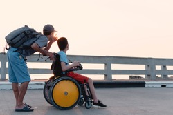 Asian special child on wheelchair is happily on Public bridge with father,Dad and son spend holiday to travel and learning about nature  outdoors, Life in the education age,Happy disabled kid concept.