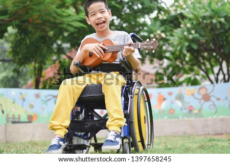 Asian special child on wheelchair is playing ukulele happily on the playground, nature background, Life in the education age of disabled children, Happy disabled kid concept. Stock photo ©