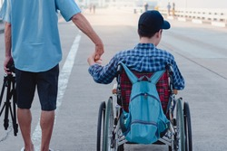 Asian special child on wheelchair wearing blue shirt and cap with backpack hold hands with father on public street, Lifestyle in the education age of disabled children, Happy disabled kid concept.