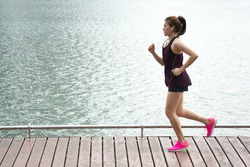 Asian sport woman jogging on lake rim in park for health