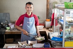 Asian stall waiters stand holding tongs while preparing side dishes for customers' orders at the stall