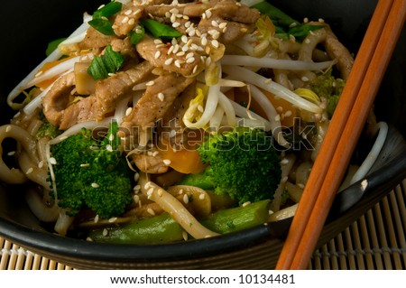 Asian stir fry with Shanghai noodles, pork, vegetables, bean sprouts and sesame seeds, with chopsticks on bamboo mat
