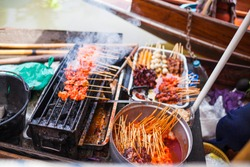asian streedfood bbq grill in an wooden canoe on amphawa floating market in thailand on a river near bangkok. Different types of satay sticks on smokey fire.