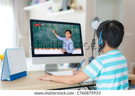 Asian  student boy video conference e-learning with teacher on computer in living room at home. E-learning ,online ,education and internet social distancing protect from COVID-19 virus.