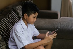 Asian student boy with school uniform sit on the sofa learning online using tab. Stay at home and social distancing during corona pandemic.
