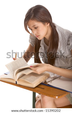 Asian student girl sitting by the desk and studying English dictionary in preparation for test, exam or spelling bee contest