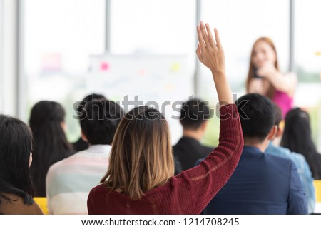 Asian student having questions in a training classroom. Rear view of Young businesswoman raised hand Up during seminar. Designer team meeting in conference. Business, Event ,Education, coaching.