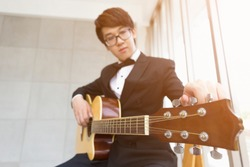 Asian student in tuxedo or elegant young fashion teenage or Young musician tuning a guitar on classroom or studio. He prepared learn Music Courses or the music competition. or audio recordings