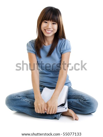 Asian student sitting on floor, with cheerful expression.