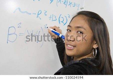 Asian student solving mathematics problem on white board