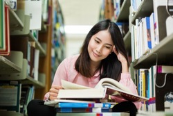 Asian student was reading in the library. She is happy and smiling
