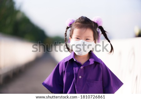 Asian student wearing white cloth mask. Child smile sweetly under  cloth mask showing through eyes. Kid go to school with new happy lifestyle (New normal). Kindergarten children aged 3 and half years. Stock photo ©