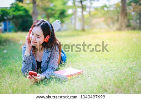 Asian student with headphones relaxing on the green grass.She is listening to music using a smertphone,chill out and leisure.
