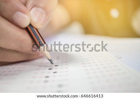 Asian Students holding pencil in hand doing multiple-choice quizzes or testing exams answer sheets exercises on old wood table In secondary school, college university classroom in education concept